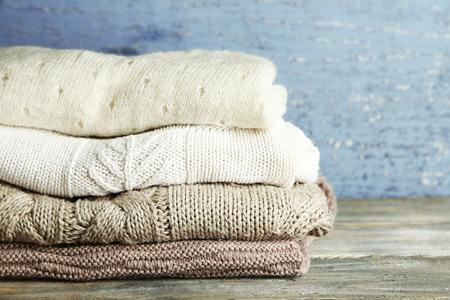 sueteres: Tejer ropa en el fondo de madera