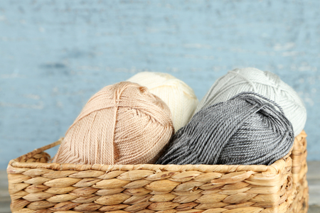 basket embroidery: Knitting yarn in basket, on wooden background
