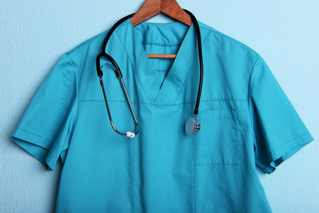 shirt hanger: Doctor shirt with stethoscope on hanger on blue background