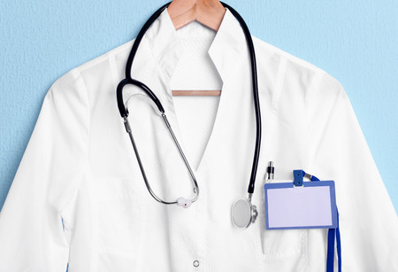 Doctor coat with stethoscope on hanger on blue background
