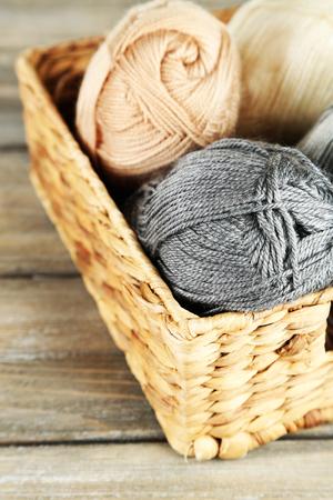 wooden basket: Knitting yarn in basket, on wooden background