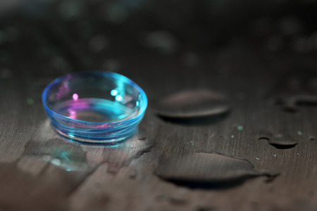 shortsightedness: Contact lens with water drops on bright background Stock Photo