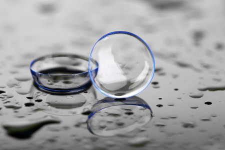 Contactlenzen met druppels water op een lichte achtergrond Stockfoto