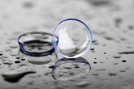 Kontaktlinsen mit Wassertropfen auf hellem Hintergrund