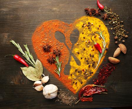 Kruiden op de tafel in de vorm van hart met een lepel silhouet, close-up Stockfoto
