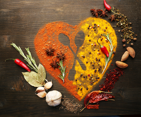 spice: Spices on table in shape of heart with spoon silhouette, close-up