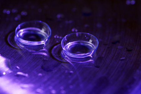 shortsightedness: Contact lenses with water drops on bright background