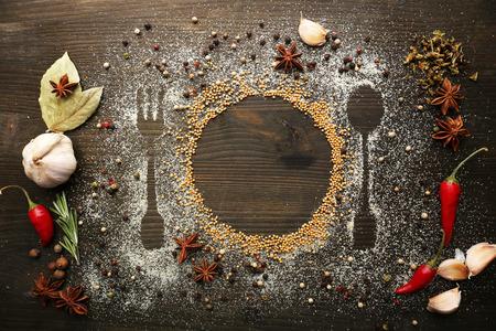comida gourmet: Especias en la mesa con cubiertos silueta, primer plano Foto de archivo