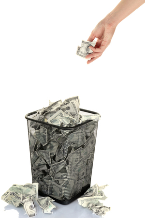inflation basket: Hand throwing money into trash can isolated on white Stock Photo