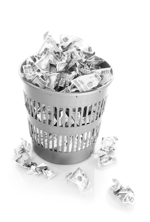 unnecessary: Money in dustbin isolated on white