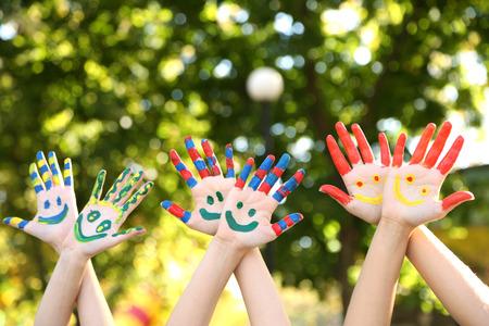 Sourire mains colorées sur fond naturel