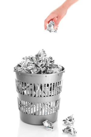 bucket of money: Hand throwing money into trash can isolated on white Stock Photo