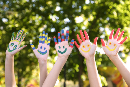 help: Smiling colorful hands on natural background
