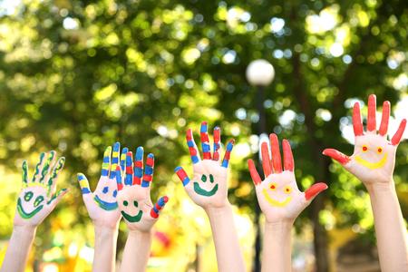 niños dibujando: Sonreír manos de colores sobre fondo natural Foto de archivo