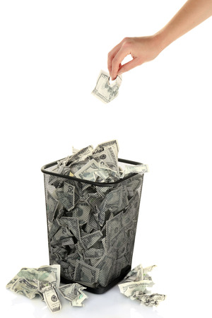 unnecessary: Hand throwing money into trash can isolated on white Stock Photo