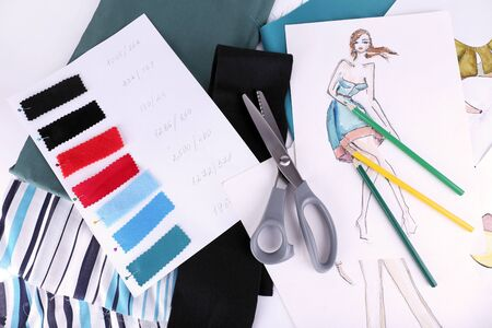 samples: Sketches of clothes and fabric samples on table Stock Photo