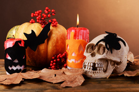 Composition of decorative skull, pumpkin, candles and Halloween decorations on wooden table, on dark color background Stock Photo