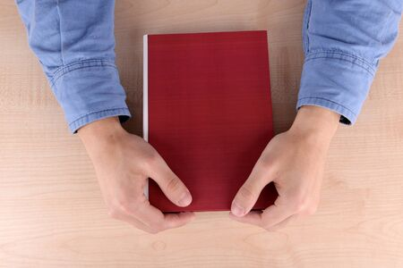 illiterate: Men reading book on wooden table background
