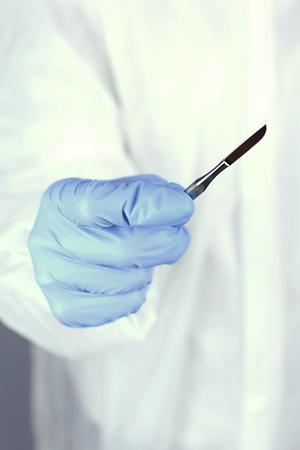 scalpel: Surgeons hand holding scalpel closeup