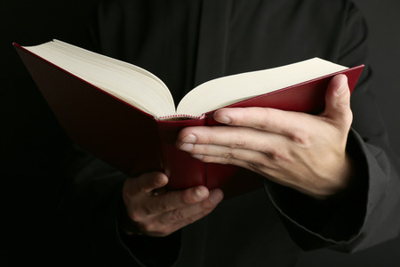 holding bible: Man holding Bible on dark background