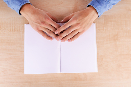 illiterate: Men reading empty open book on wooden table background