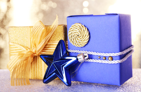 Blue and golden gift boxes and Christmas toy on table on shiny background Stock Photo