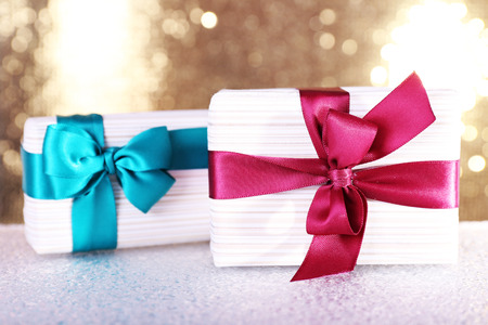 vinous: Gift boxes with vinous and blue ribbons and Christmas toy on table on shiny background
