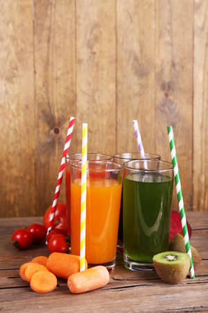 natural juices: Fruit and vegetable juice in glasses and fresh fruits and vegetables on table on wooden background Stock Photo