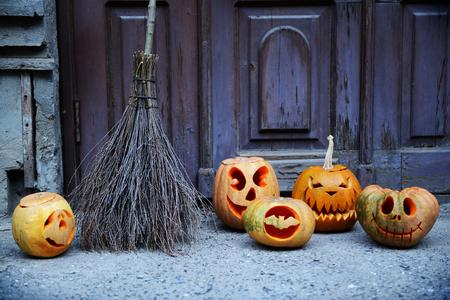 カボチャとほうきを古い木製のドアの背景にハロウィーンの休日のため