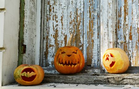 terrify: Pumpkins for holiday Halloween on old wooden door background