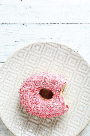 bitten: Bitten delicious donut on plate on wooden table close-up Stock Photo