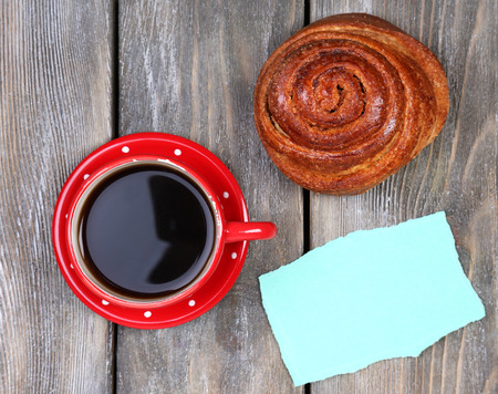 sweet good: Composition of coffee, fresh bun and paper card on wooden background