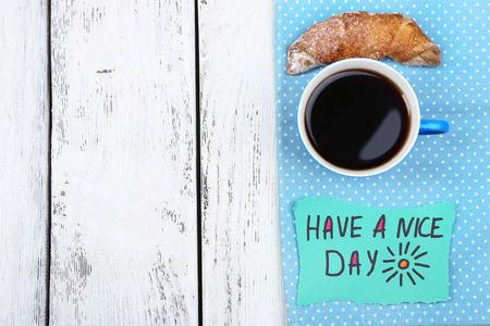 comida rica: Composición de café, croissant fresco y tarjeta de papel en la servilleta, sobre fondo de madera Foto de archivo
