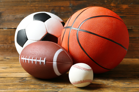 Sports balls on wooden background Imagens