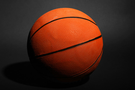 different goals: Basketball ball on black background