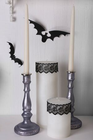 witchery: Candles and paper bats on table on white wall background Stock Photo