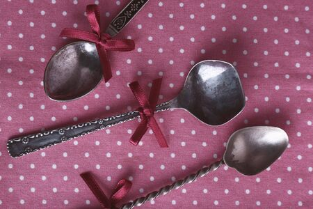 polka dot fabric: Metal spoons on pink polka dot fabric background Stock Photo