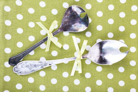 polka dot fabric: Metal spoons on polka dot fabric background