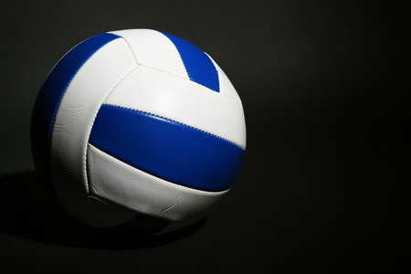 different goals: Volleyball ball on black background