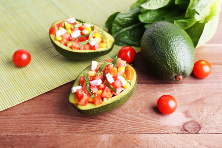 food supplement: Tasty salad in avocado on table and bamboo napkin close-up Stock Photo