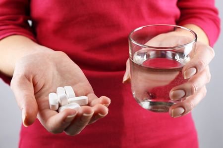 vitamin pill: Hands with pills and glass of water Stock Photo