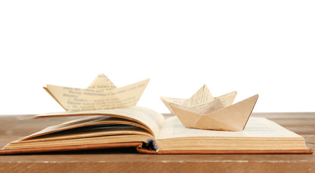 Origami boats on old book on wooden table, on white background 版權商用圖片
