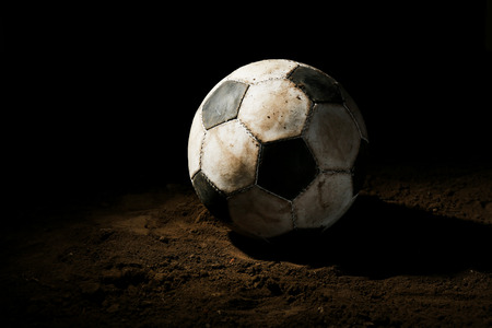 beat the competition: Soccer ball on ground on dark background Stock Photo