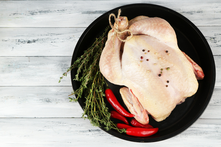 roasted chicken: Raw chicken on wooden table