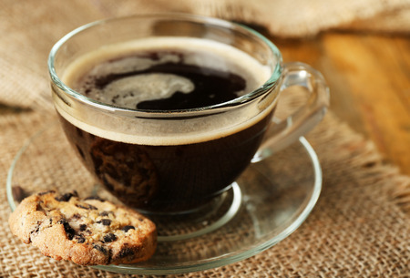 Tazza di caffè di vetro e biscotto saporito su fondo di legno