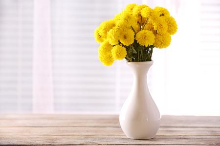 Mooie bloemen in de vaas met licht uit raam