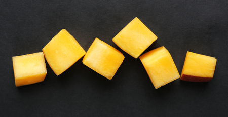 fruit juices: Mango slices on black background