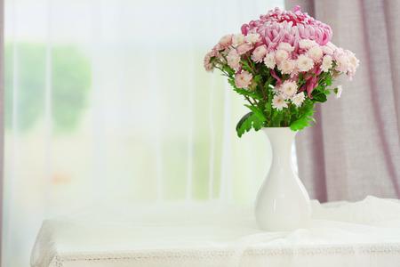 Hermosas flores en florero con la luz de la ventana Foto de archivo