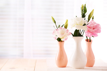 Beautiful flowers in vases with light from window Banco de Imagens