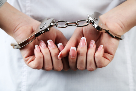 handcuffed: Female hands are handcuffed at  wrist, close-up